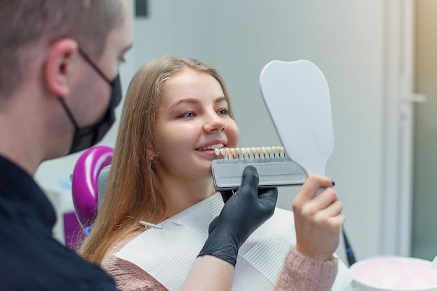 Dentista che abbina il colore dei denti dei pazienti con la tavolozza in ufficio