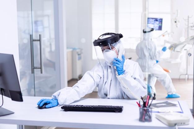 Infermiera dentista vestita di dpi nella clinica di stomatologia durante il covid-19 che discute con il paziente al telefono. squadra di medicina che indossa indumenti di protezione contro la pandemia di coronavirus nella ricezione dentale come sicurezza