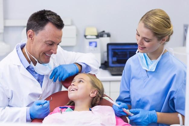 Dentista e infermiere che interagiscono con un giovane paziente