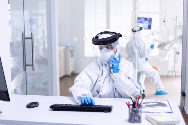 Infermiera dentista in tuta dpi che discute con il paziente al telefono durante il covid19. squadra di medicina che indossa indumenti di protezione contro la pandemia di coronavirus nella ricezione dentale come precauzione di sicurezza.