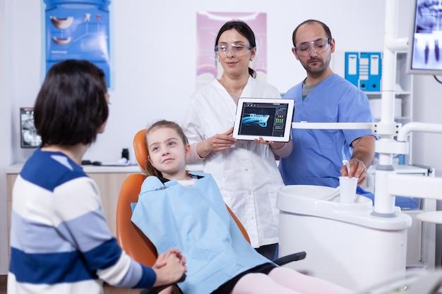 Dentista e paziente commentando il trattamento della cavità nell'applicazione tablet dopo la consultazione. stomatologo che spiega la diagnosi dei denti alla madre del bambino in clinica sanitaria che tiene i raggi x.