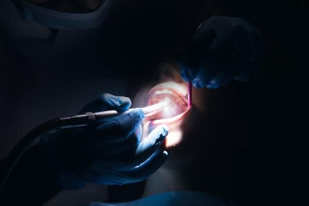 Il dentista esegue un intervento chirurgico in una stanza buia