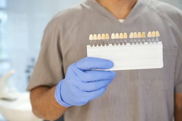 Dentista in posa con il kit per sbiancare i denti nel suo ufficio