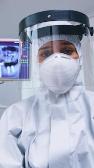Dentista pov in tuta covid che esamina l'igiene della bocca utilizzando strumenti dentali in ufficio stomatologico con nuova normalità. stomatologo che indossa indumenti di sicurezza contro il coronavirus durante il controllo sanitario del paziente.