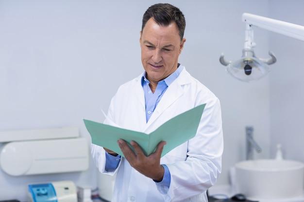 Dentista che legge il rapporto dentale