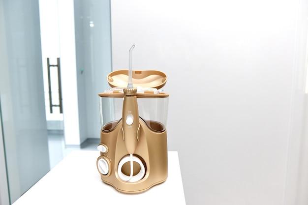 L'irrigatore a sprinkler dorato del dentista si trova su un tavolo su uno sfondo bianco brillante