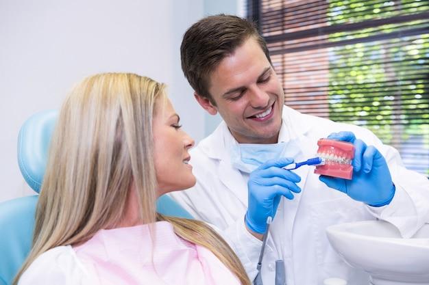 Dentista che mostra la muffa dentale al paziente