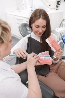 Dentista che mostra come lavarsi i denti sul modello dentale alla sua paziente di sesso femminile