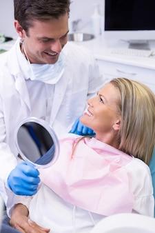 Dentista che mostra specchio al paziente felice