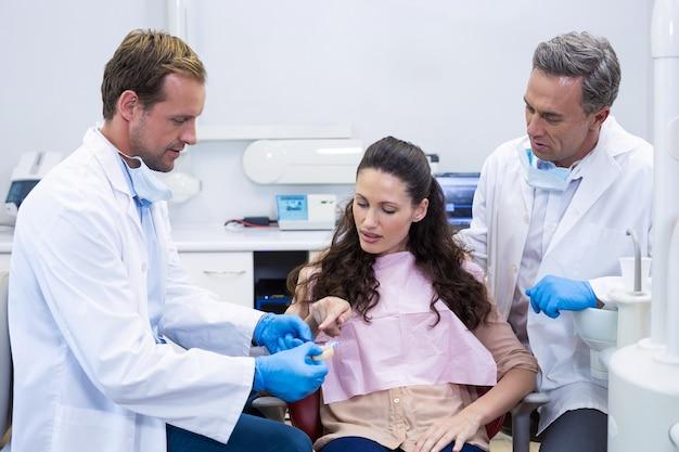 Dentista che mostra i denti del modello al paziente