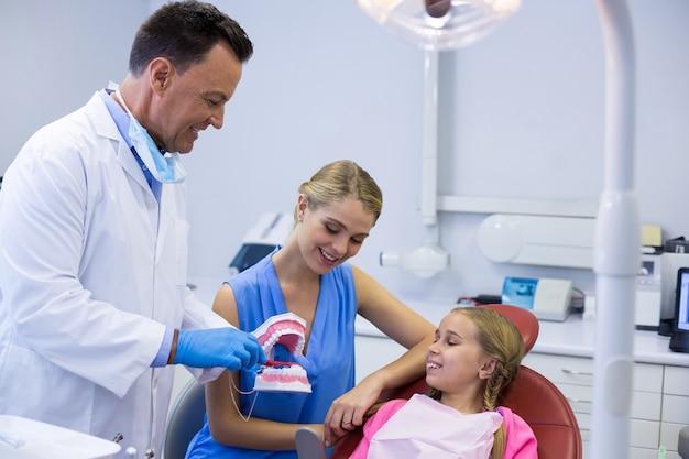 Dentista che mostra al giovane paziente come lavarsi i denti