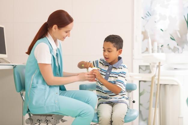 Dentista sorridente. dentista bambino che sorride mentre un ragazzo carino usa lo spazzolino da denti sul modello del dente tooth