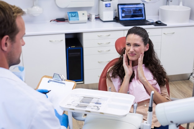 Dentista parlando al paziente di sesso femminile