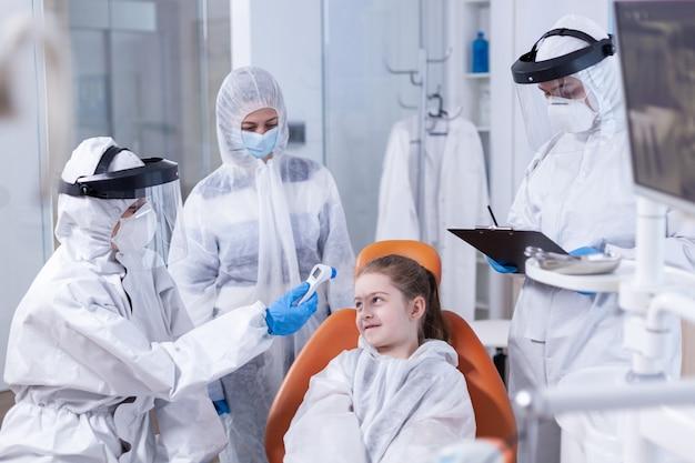 Dentista che parla della temperatura corporea di una bambina usando un termometro digitale vestito in modo da coprire tutto contro il coronavirus. stomatologo durante il covid19 che indossa una tuta in dpi facendo la procedura dei denti del bambino seduto