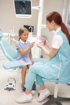 Ragazza di insegnamento del dentista. dentista per bambini dai capelli rossi che insegna alla ragazza a usare lo spazzolino da denti due volte al giorno