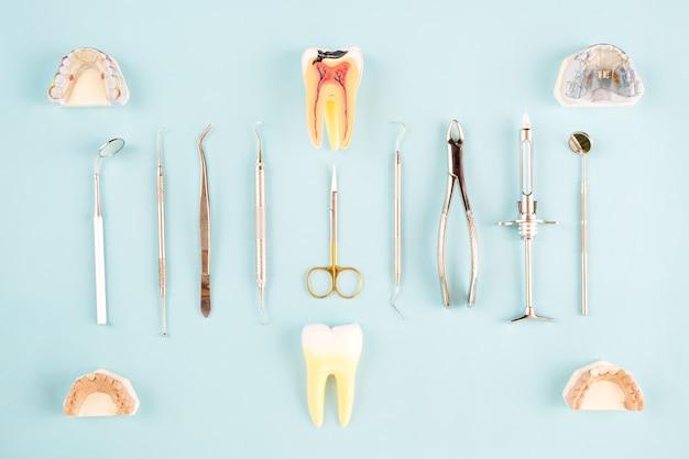Strumenti del dentista e protesico su sfondo di colore, piatto posare, vista dall'alto.