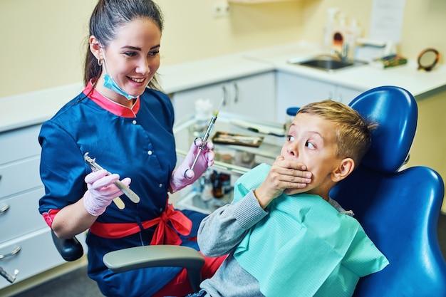 Dentista che cura i suoi denti e riempie la cavità nella clinica moderna