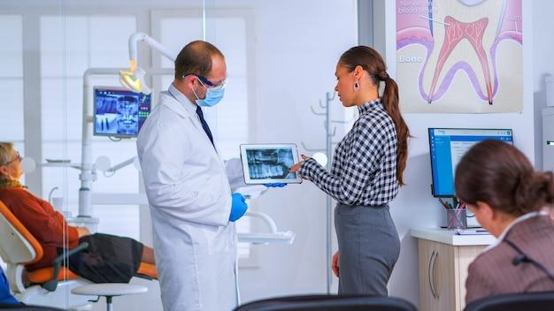 Dentista nella sala d'attesa dello studio dentistico che parla con una paziente che esamina l'immagine a raggi x su tablet mentre i pazienti sono seduti su sedie nell'area di ricezione. medico che mostra radiografia dentale, gadget moderno
