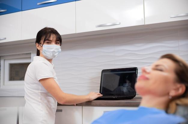 Un dentista che indossa una mascherina medica protettiva presso l'ufficio di odontoiatria. un medico in una maschera protettiva che lavora al laptop e consulta un paziente su una poltrona odontoiatrica