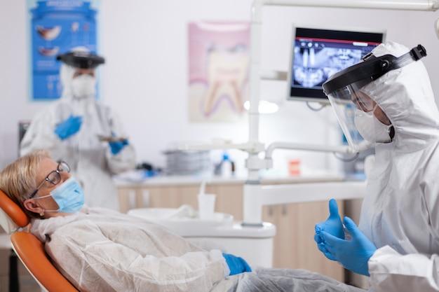 Dentista che indossa indumenti di sicurezza contro il coronavirus che parla del trattamento dei denti. donna anziana in uniforme protettiva durante la visita medica in clinica odontoiatrica.