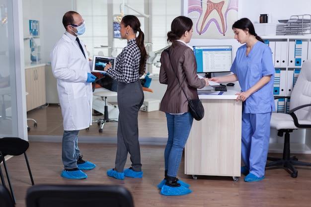 Dentista con maschera facciale che punta ai raggi x della radiografia digitale dei denti al paziente nell'area di attesa della clinica ...