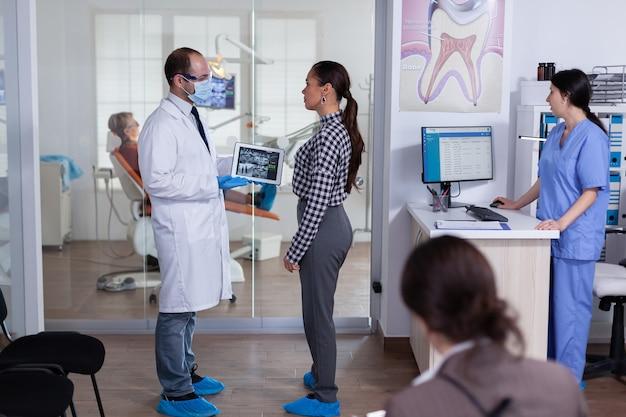 Dentista con maschera facciale che mostra i raggi x dentali del paziente