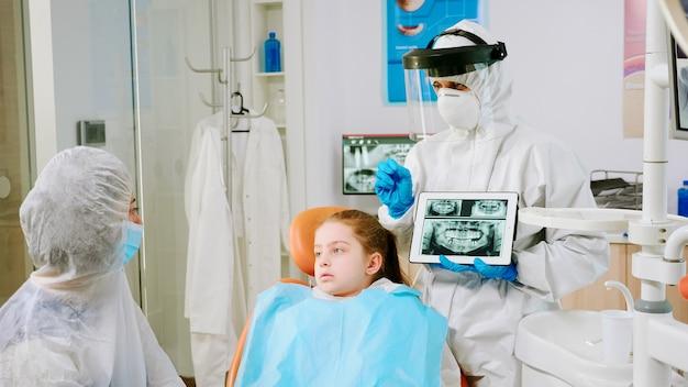 Dentista con visiera che spiega l'immagine radiografica panoramica della bocca alla madre del bambino paziente durante la pandemia globale. stomatologo che parla con una donna che indossa tuta, tuta, tuta protettiva, maschera, guanti