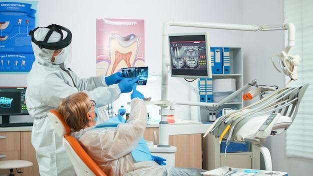 Dentista con visiera che esamina l'immagine radiografica panoramica della bocca al paziente durante la pandemia globale. assistente e medico che parlano con una donna anziana che indossa tuta, tuta, tuta protettiva, maschera, guanti