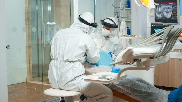 Dentista con controllo medico generale problema dei denti del paziente anziano durante la pandemia di coronavirus. medico e infermiere che lavorano indossando tuta, visiera, tuta protettiva, maschera, guanti in studio dentistico