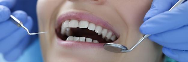 Dentista con strumenti in acciaio nelle sue mani esamina il primo piano dei denti del paziente