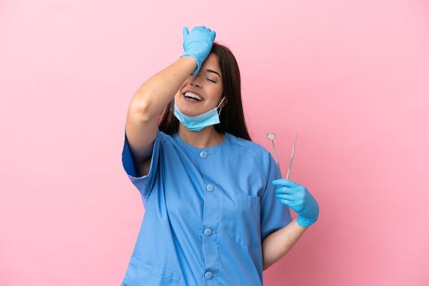 La donna del dentista che tiene gli strumenti isolati su sfondo rosa ha realizzato qualcosa e intendeva la soluzione