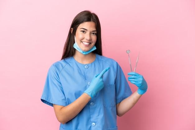 Donna del dentista che tiene gli strumenti isolati su sfondo rosa che punta al lato per presentare un prodotto