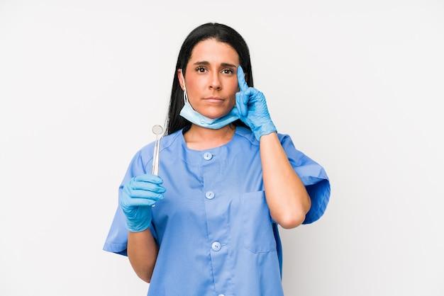 Dentista donna isolata sul muro bianco che punta tempio con il dito, pensando, concentrato su un compito.
