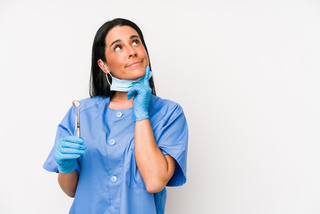 La donna del dentista isolata sulla parete bianca si è rilassata pensando a qualcosa guardando uno spazio di copia