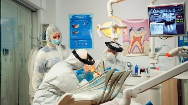 Medico di odontoiatria in tuta protettiva che utilizza strumenti dentali sterilizzati che esaminano un bambino durante la pandemia di coronavirus. equipe medica che parla con una donna che indossa visiera, tuta, maschera e guanti