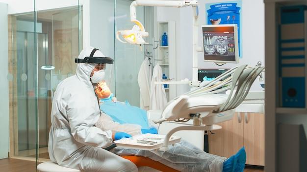 Medico di odontoiatria in tuta protettiva che utilizza strumenti dentali sterilizzati che esaminano il paziente anziano durante la pandemia di coronavirus. equipe medica che parla con una donna che indossa visiera, tuta, maschera e guanti