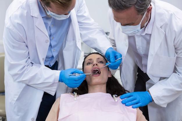 Dentisti che esaminano un paziente femminile con gli strumenti
