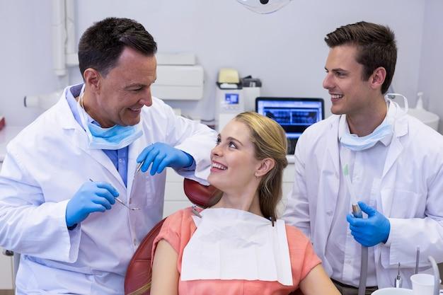 Dentisti che interagiscono con il paziente femminile