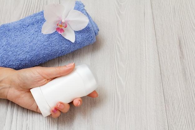 Deodorante in mano della donna, asciugamano blu con orchidea su uno sfondo di legno grigio con spazio di copia. cosmetici e accessori donna. vista dall'alto.