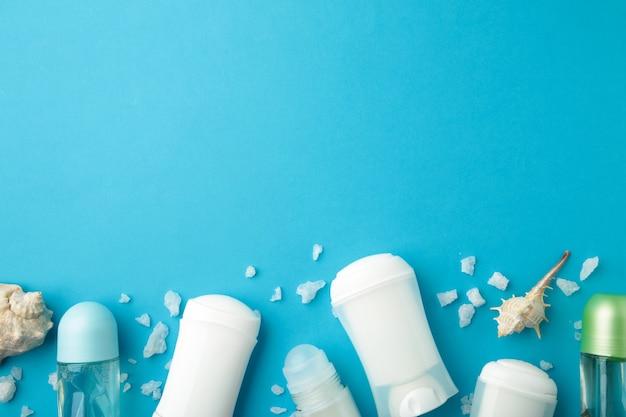 Deodoranti per donne e conchiglie sulla superficie blu con spazio di copia