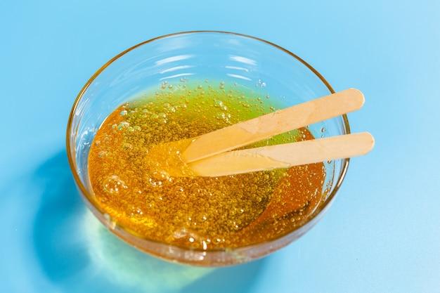 Depilazione e concetto di bellezza - primo piano di pasta di zucchero o cera di miele per la rimozione dei capelli con spatola