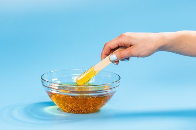 Depilazione e concetto di bellezza. pasta di zucchero o cera al miele per depilazione spatola con legno