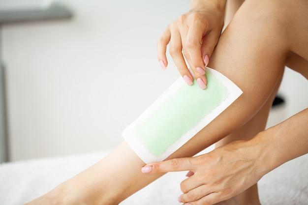 Procedura di depilazione con cera sulle gambe