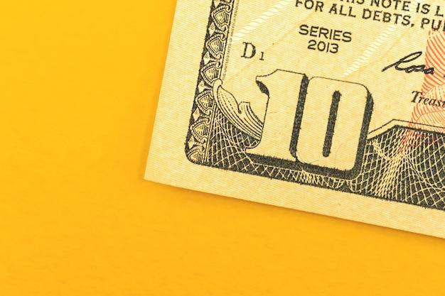 Deposito di una piccola somma di denaro, primo piano della banconota da dieci dollari su uno sfondo giallo, foto vista dall'alto