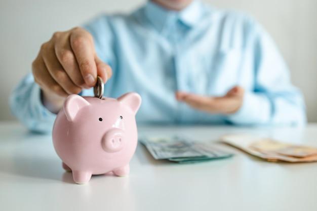 Depositare denaro in un salvadanaio su un tavolo di legno a casa risparmiando denaro