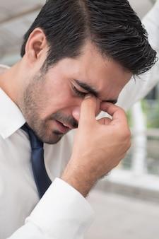 Uomo d'affari asiatico depresso; ritratto di un uomo asiatico indiano malato con depressione che soffre di mal di testa, vertigini, postumi di una sbornia, emicrania, stress