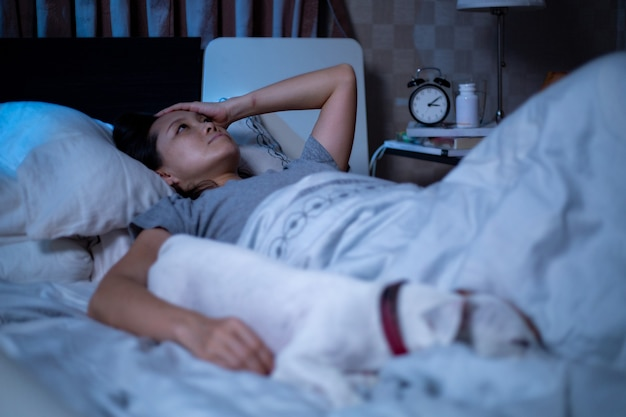 La donna asiatica depressa non riesce a dormire sul letto. sindrome di insonnia insonne dopo infelice e preoccupata per il suo stile di vita. l'adulto sente tristezza. cattiva emozione. proprietario e cane dormono.