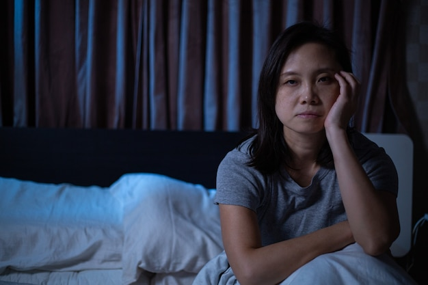 La donna asiatica depressa non riesce a dormire sul letto. sindrome di insonnia insonne dopo l'infelicità e la preoccupazione per il suo stile di vita. l'adulto sente tristezza. cattiva emozione.