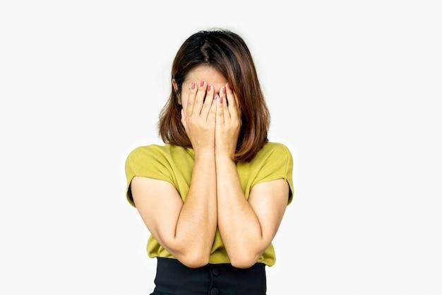 Mano di donna asiatica depressa che copre il viso