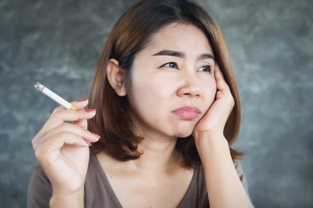 Donna asiatica depressa fumo di sigaretta con la faccia infelice